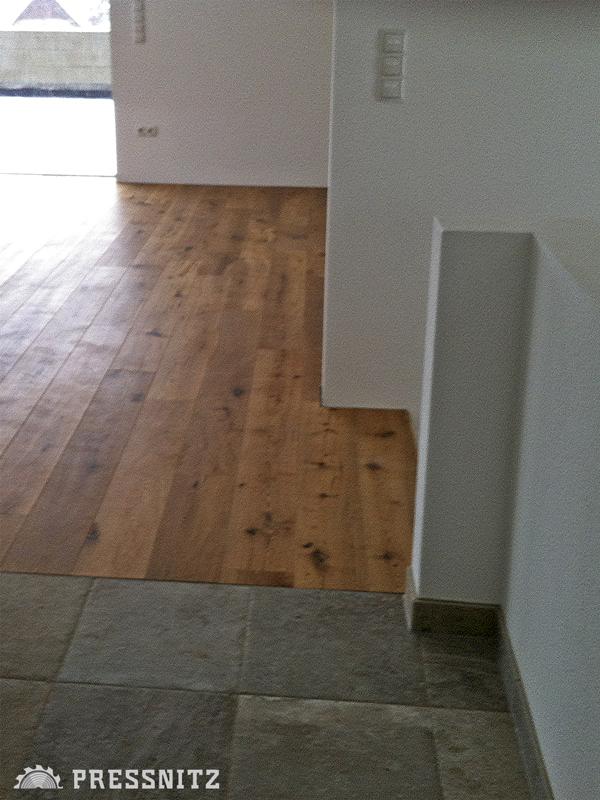 Ansicht Bodenübergang vom grauen Fliesenboden des Vorraums zum Wohnraum mit der Landhausdiele